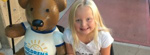 """A young girl sitting on a bench beside a teddy bear wearing a shirt that says """"BC Children's Hospital"""""""