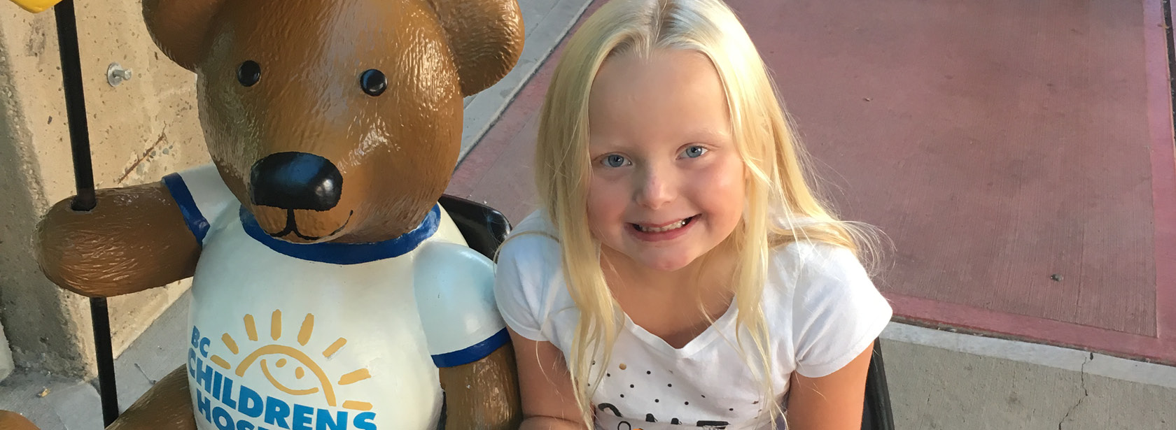 "A young girl sitting on a bench beside a teddy bear wearing a shirt that says ""BC Children's Hospital"""