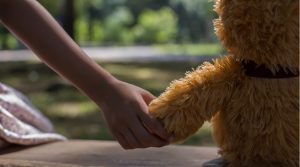 A child sits on a bench, holding her teddy bear's hand