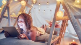 A girl is on a video conference call on her laptop while lying down in a homemade tent in her bedroom