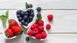 Small heart-shaped bowls with strawberries, blueberries, and raspberries