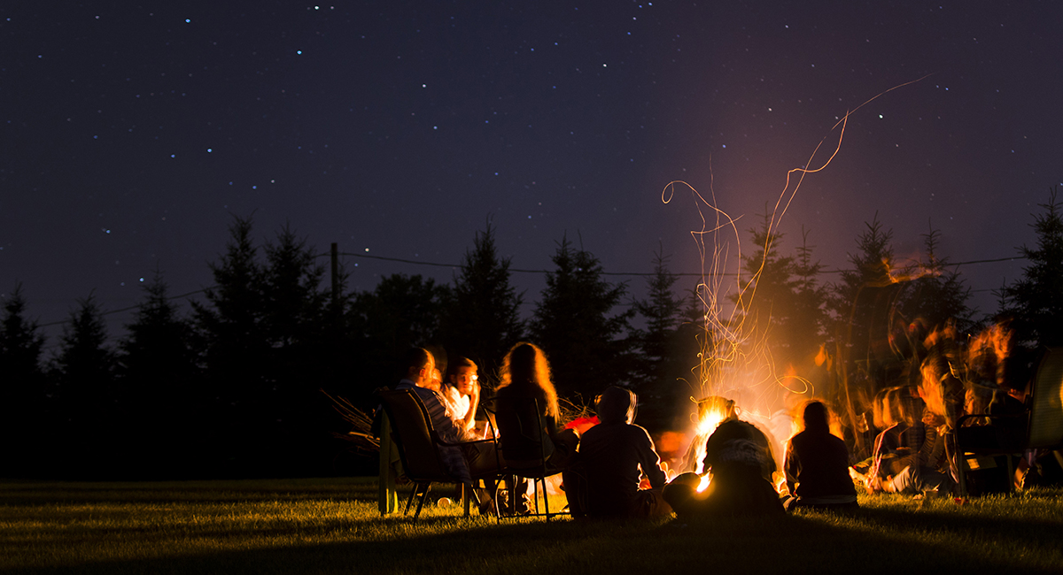 A group of campers sitting around a campfire